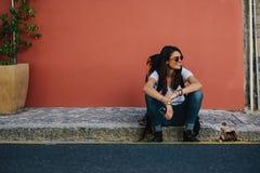 Kvinnlig handelsresande som vilar på trottoaren royaltyfri fotografi