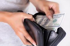 Kvinnlig handhåll en svart handväska med Amerika dollar och lön royaltyfria foton