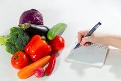 Kvinnlig handhandstil bantar plan i anteckningsbok mot sammansättning för den nya grönsaken Royaltyfri Fotografi
