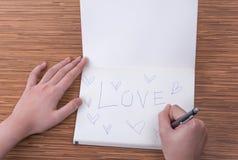 Kvinnlig handhandstil i anteckningsbok på tabellen royaltyfri fotografi