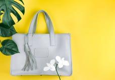 Kvinnlig handväska med naturliga blommor och det gröna bladet royaltyfri fotografi