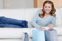 kvinnlig henne liggande nästa shopping som ler till Royaltyfri Bild