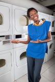 Kvinnlig hjälpreda som gör en gest i tvätteri fotografering för bildbyråer
