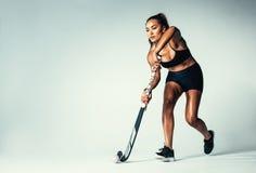 Kvinnlig hockeyspelare som dreglar bollen royaltyfria bilder