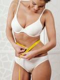 Kvinnlig i hennes underkläder som mäter hennes midja arkivbilder