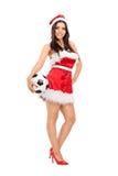 Kvinnlig i jultomtendräkten som rymmer en fotboll Royaltyfri Bild