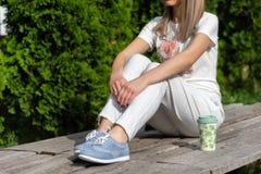 Kvinnlig i randiga flåsanden, blåa gymnastikskor och t-skjortan som sitter på bänken bredvid koppen kaffe och vila arkivfoton