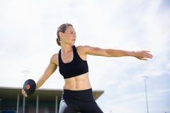 Kvinnlig idrottsman nen omkring som kastar en diskus royaltyfri foto