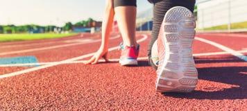 Kvinnlig idrottsman nen på den startande linjen av ett stadionspår Arkivfoton