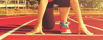 Kvinnlig idrottsman nen på den startande linjen av ett stadionspår Arkivfoto