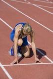 Kvinnlig idrottsman nen Ready To Race på spår Royaltyfri Fotografi