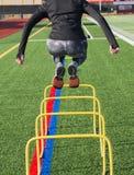 Kvinnlig idrottsman nen som bakifrån hoppar över utbildningshäckar arkivfoto