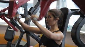 Kvinnlig idrottsman nen som inomhus gör placerad främre press på maskinen i idrottshall stock video