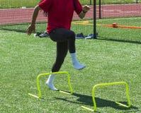 Kvinnlig idrottsman nen som kliver över kortkorthäckar i sockor Royaltyfria Foton