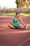 Kvinnlig idrottsman nen som sträcker på ett rinnande spår Arkivfoto