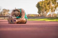 Kvinnlig idrottsman nen som sträcker på ett rinnande spår Royaltyfria Bilder