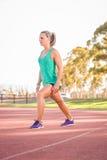 Kvinnlig idrottsman nen som sträcker på ett rinnande spår Royaltyfri Bild