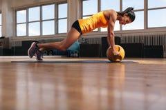 Kvinnlig idrottsman nen som utarbetar på hennes kärnamuskel Royaltyfria Foton