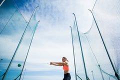 Kvinnlig idrottsman nen som utför ett hammarekast Royaltyfri Foto