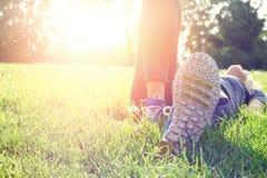 Kvinnlig idrottsman nen som vilar och kopplar av efter genomkörare Kvinna som ner ligger på gräs Sund livsstil och lyckabegrepp Fotografering för Bildbyråer