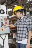 Kvinnlig industriarbetare som fungerar den fabriks- maskinen på fabriken Fotografering för Bildbyråer