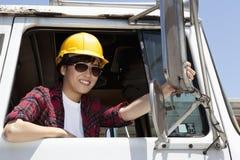Kvinnlig industriarbetare som justerar spegeln, medan sitta, i att logga lastbilen Arkivbilder