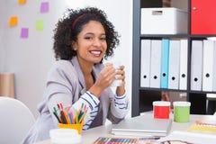 Kvinnlig inreformgivare med kaffekoppen på skrivbordet royaltyfria foton