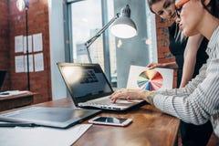 Kvinnlig inreformgivare som arbetar med hållande ögonen på bilder för en kund genom att använda bärbar datorsammanträde på den mo arkivbild