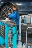 Kvinnlig inställd bil för mekaniker Changing Tire From i garage royaltyfria bilder