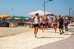Kvinnlig instruktör- och grupp människorspring på en strandbana utomhus royaltyfri foto