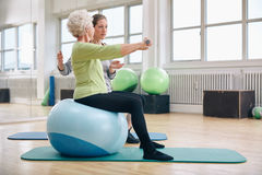 Kvinnlig instruktör som hjälper lyftande vikter för hög kvinna Arkivbild