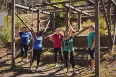 Kvinnlig instruktör som instruerar kvinnor, i att klättra ett rep i kängalägret royaltyfri bild