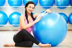 Kvinnlig instruktörstående med konditionbollen Arkivbild