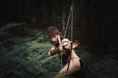 Kvinnlig jägare som siktar med pilbågen arkivfoto