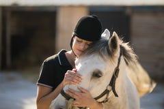 Kvinnlig jockey som omfamnar hästen på ladugården royaltyfri foto