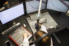 Kvinnlig jockey Using Music Mixers och skärmar i radiostudio Royaltyfri Fotografi