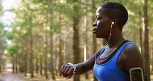 Kvinnlig jogger som använder smartwatch i skogen 4k arkivfilmer
