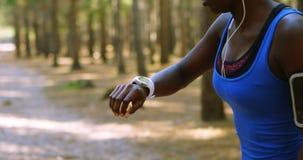 Kvinnlig jogger som kontrollerar tid på smartwatch i skogen 4k lager videofilmer
