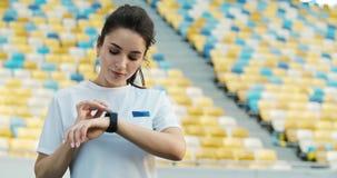 Kvinnlig Jogger som ställer in Smartwatch arkivfilmer