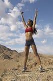 Kvinnlig Jogger som utomhus sträcker henne armar Arkivfoton