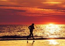 Kvinnlig joggerspring på stranden på solnedgången Royaltyfri Foto