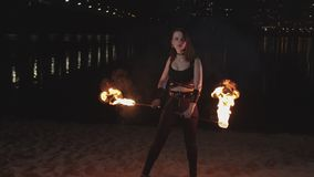 Kvinnlig jonglör som lyfter brinnande facklor från sand lager videofilmer