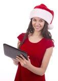 Kvinnlig jultomten genom att använda minnestavlan Fotografering för Bildbyråer