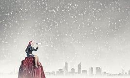 Kvinnlig jultomten som gör meddelande arkivfoton