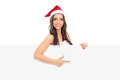 Kvinnlig jultomten som pekar på en panel med hennes finger Arkivfoto