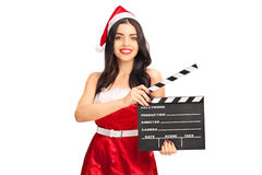 Kvinnlig jultomten som rymmer en filmclapperboard Arkivfoto