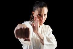 Kvinnlig kämpe som utför karateslagställning Arkivbild