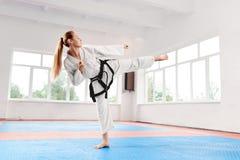 Kvinnlig kämpe som utför spark med lyftt legr som förbättrar teknik av kampen royaltyfria foton
