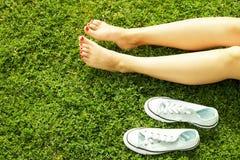 Kvinnlig kal fot på mawed gräsmattagräs Den unga kvinnan som utomhus barfota vilar, tar ett avbrottsbegrepp Student på högskolaun royaltyfria foton