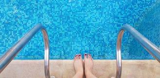 Kvinnlig kal fot som står på kanten av simbassänghalvan som är klar att skriva in arkivbilder